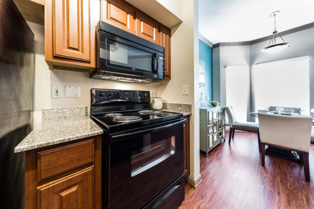 Cozy kitchen area with wood cabinets and flooring at Marquis on Park Row in Houston, Texas