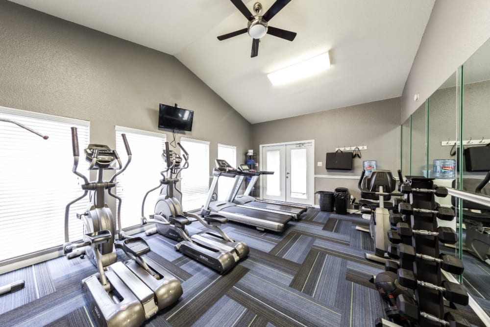 Cardio machines and free weights section in fitness room at Austin Midtown in Austin, Texas