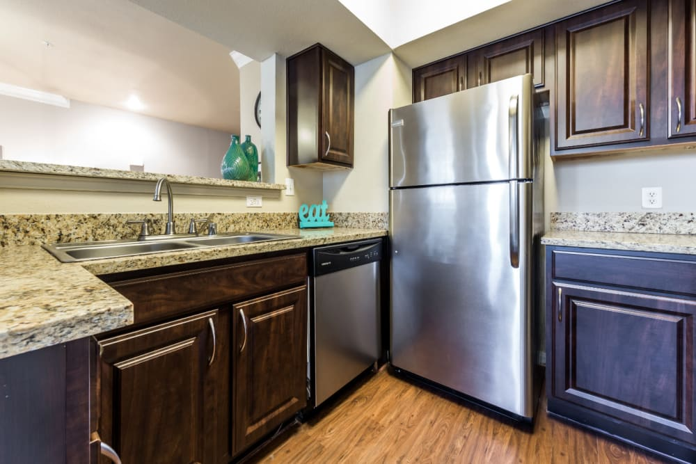 Modern kitchen with stainless steel appliances, granite counter tops, and wood flooring at Marquis at Stonegate in Fort Worth, Texas