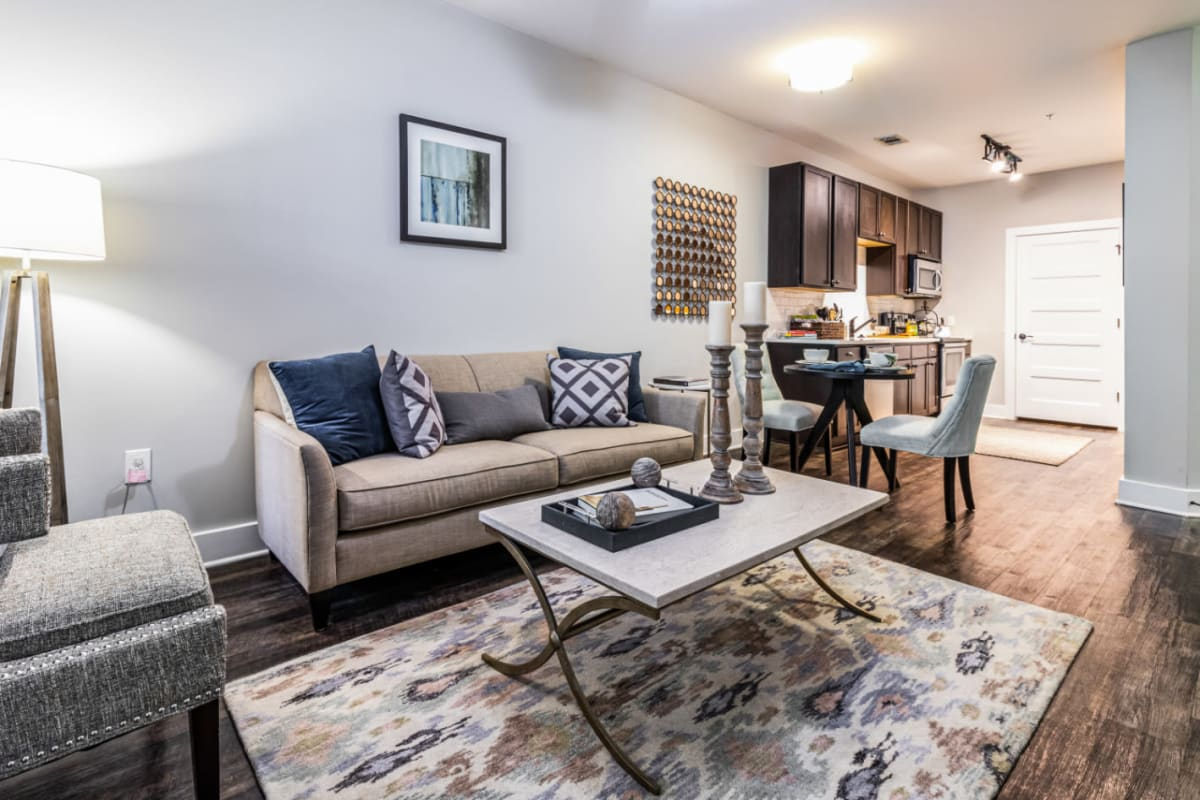 Open plan living, dining, and kitchen areas with wood flooring at Marquis at Buckhead in Atlanta, Georgia
