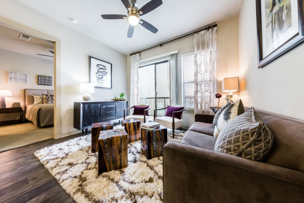 Spacious living room modernly decorated with access to private balcony at Marq Uptown in Austin, Texas