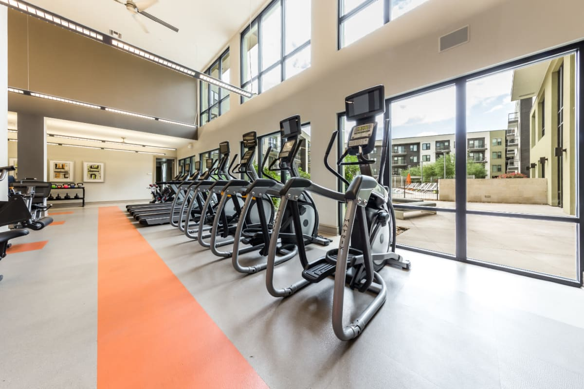 Multiple elliptical and treadmills lined up facing windows with view of pool deck at Marq Uptown in Austin, Texas