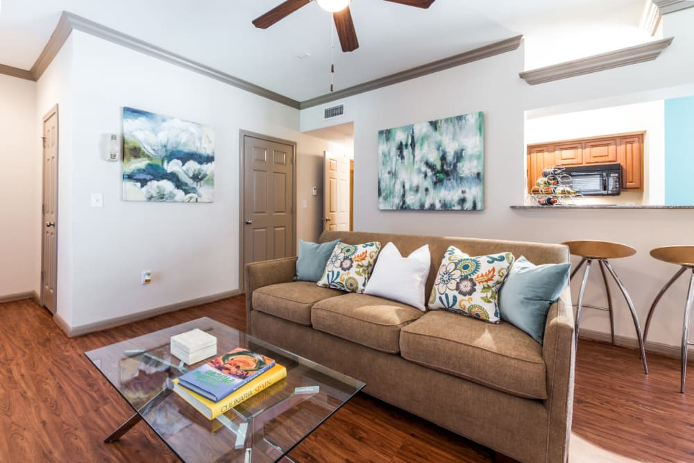 Bright and cozy living room with wood flooring and ceiling fan at Marquis on Park Row in Houston, Texas