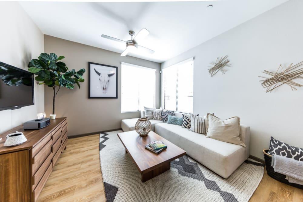 Sleek style living room with large windows and wood flooring at Marquis at Desert Ridge in Phoenix, Arizona