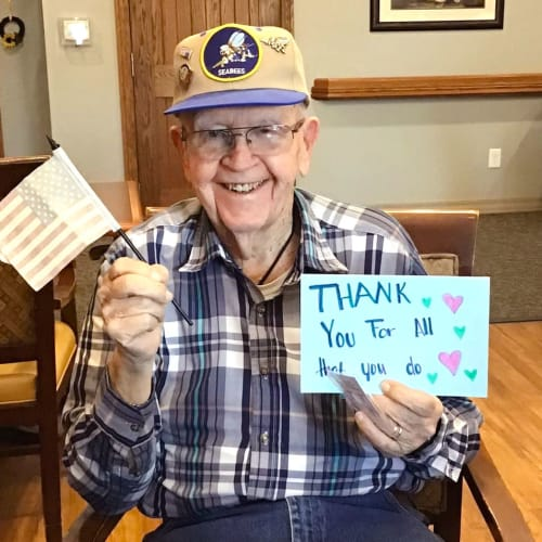Resident holding a thank you note and a mini american flag at Glen Carr House Memory Care in Derby, Kansas