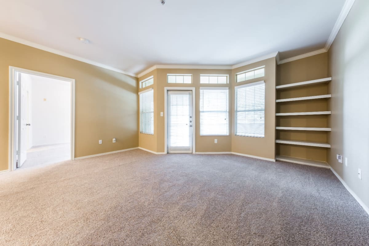 Bright and open carpeted living area with built-in shelves at Marquis at Barton Trails in Austin, Texas