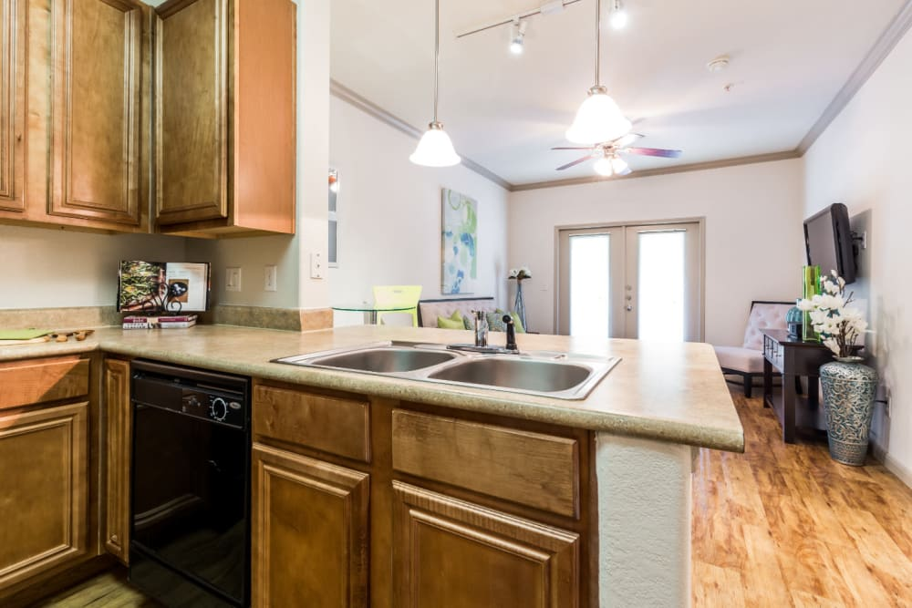 Bright kitchen with wood flooring facing living area at Marquis at Clear Lake in Webster, Texas