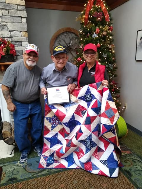 Two Veterans photographed with a handmade quilt at Willow Creek Senior Living in Elizabethtown, KY