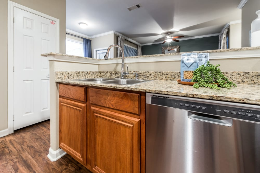 Modern style kitchen with stainless steel appliances, granite countertops, and wood flooring at Marquis at The Cascades in Tyler, Texas