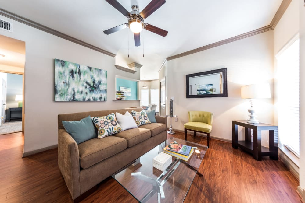 Bright and cheerful living room with wood flooring and ceiling fan at Marquis on Park Row in Houston, Texas