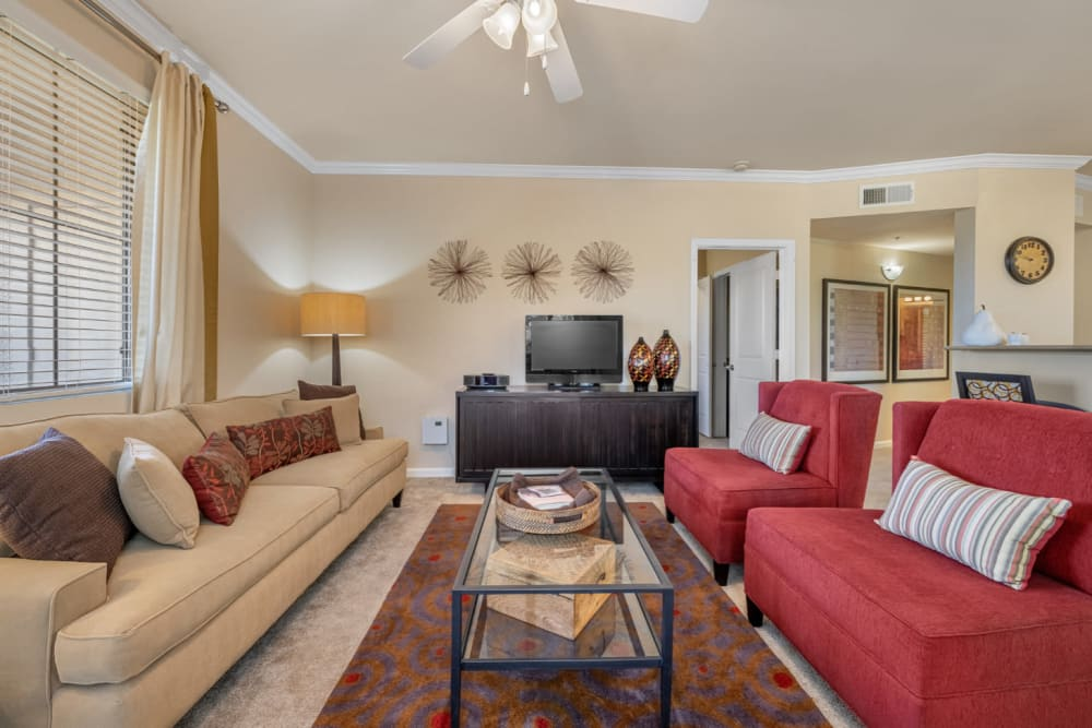 Carpeted living room with earth tone style furniture at Marquis at Sonoran Preserve in Phoenix, Arizona