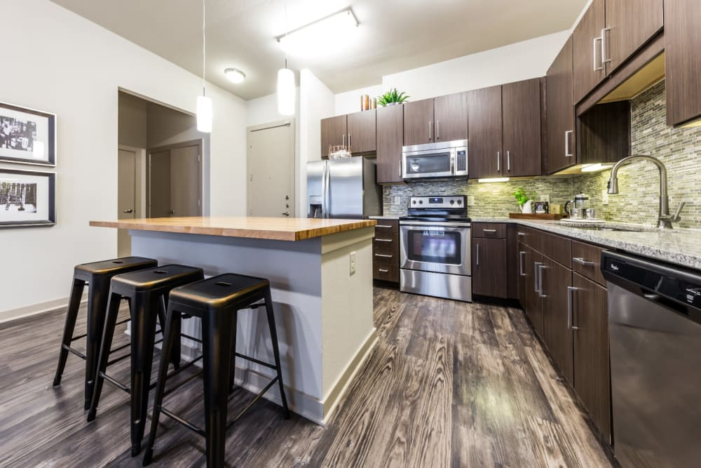 Spacious kitchen with kitchen island and counter stools at Marq Uptown in Austin, Texas
