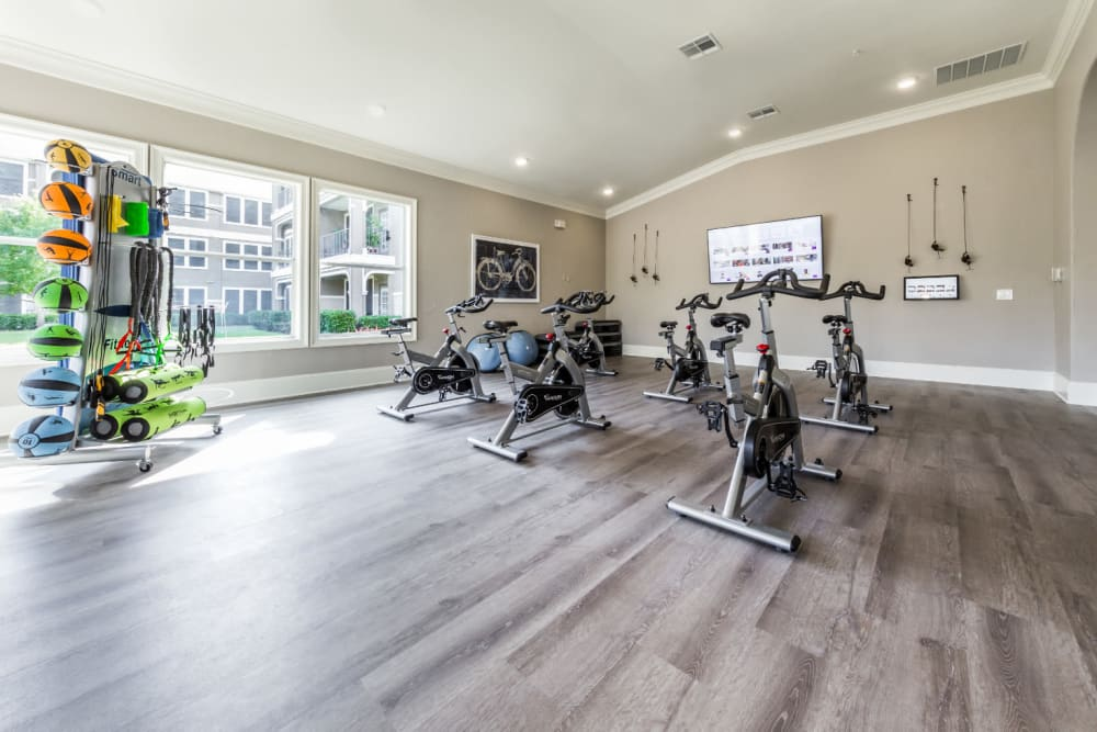 Spin bikes facing monitor in fitness room at Marquis at The Cascades in Tyler, Texas