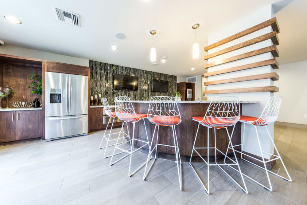 Kitchen island with tall counter chairs in community clubhouse at Marq Uptown in Austin, Texas