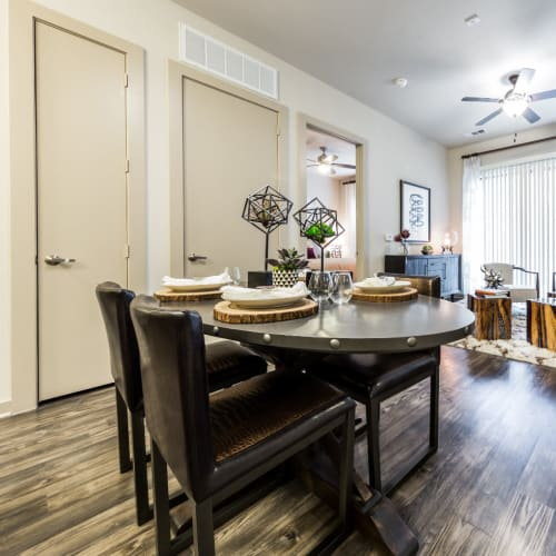 Dining table on wood flooring overlooking living room area at Marq Uptown in Austin, Texas