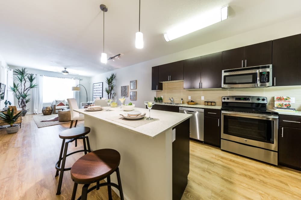 Modern kitchen with island and counter bar stools at Marquis at Desert Ridge in Phoenix, Arizona