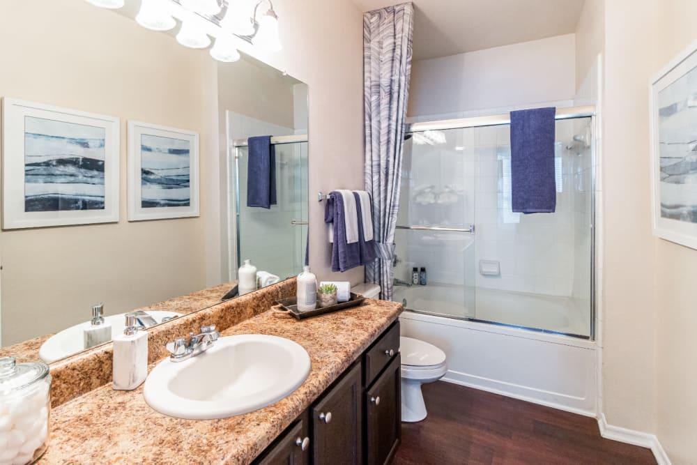 Bright bathroom with wood cabinets and flooring at Marquis of Carmel Valley in Charlotte, North Carolina