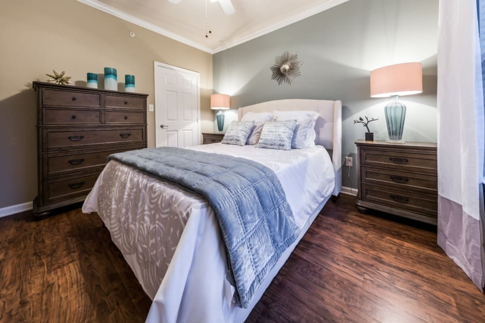 Large bedroom with wood flooring and ceiling fan at Marquis at The Cascades in Tyler, Texas