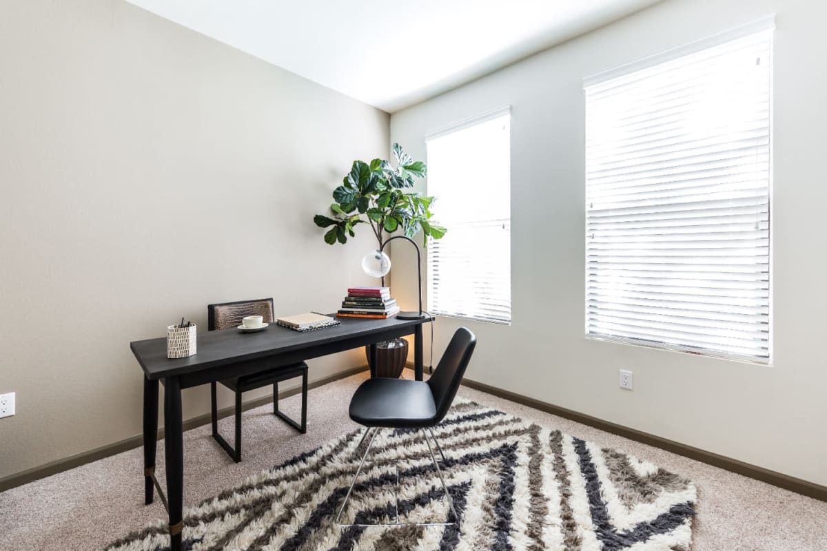 Carpeted bedroom with office set up and large windows at Marquis at Desert Ridge in Phoenix, Arizona