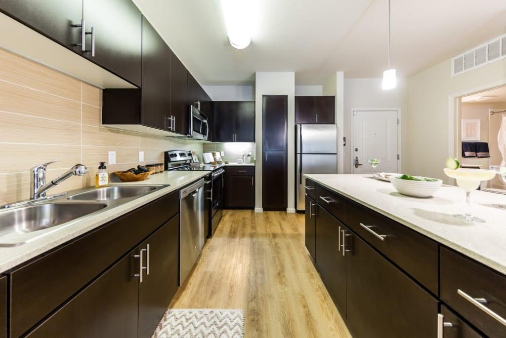 Sleek style living room with wood flooring and island at Marquis at Desert Ridge in Phoenix, Arizona