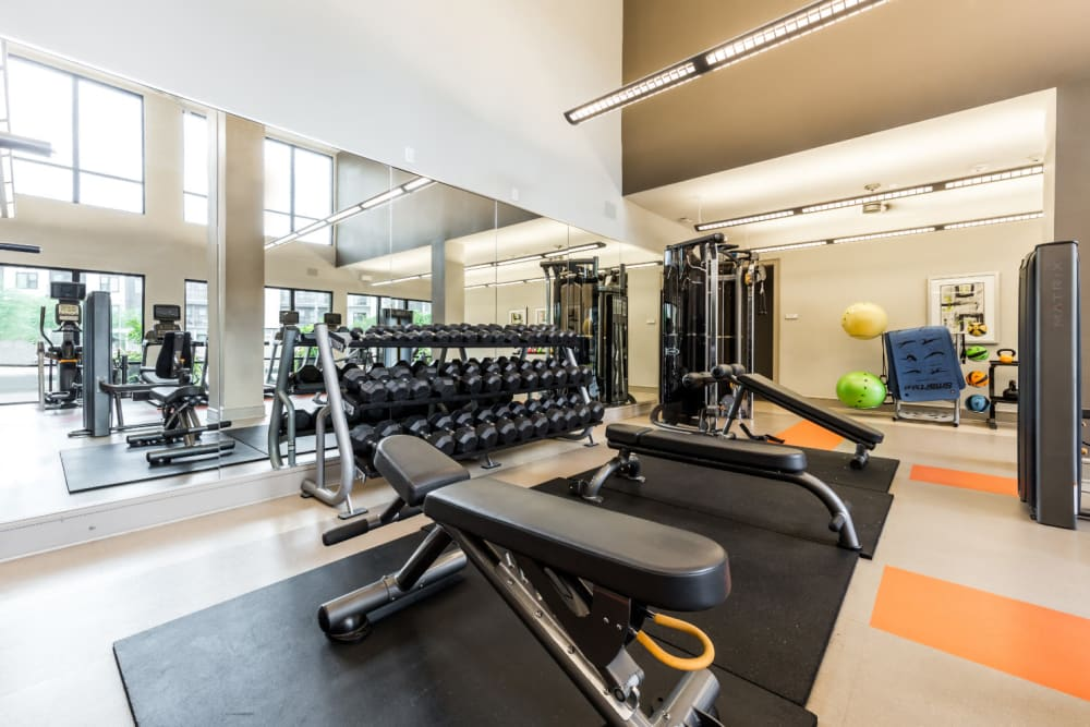 Free weights and benches with large mirror in fitness room at Marq Uptown in Austin, Texas