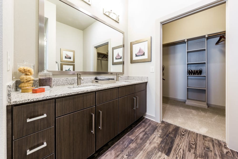 Large bathroom with double sinks and walkway to large walk-in closet at Marq Uptown in Austin, Texas