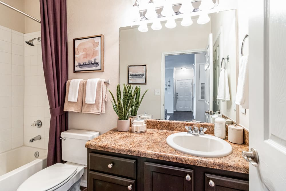 Bright bathroom with wood cabinets at Marquis of Carmel Valley in Charlotte, North Carolina