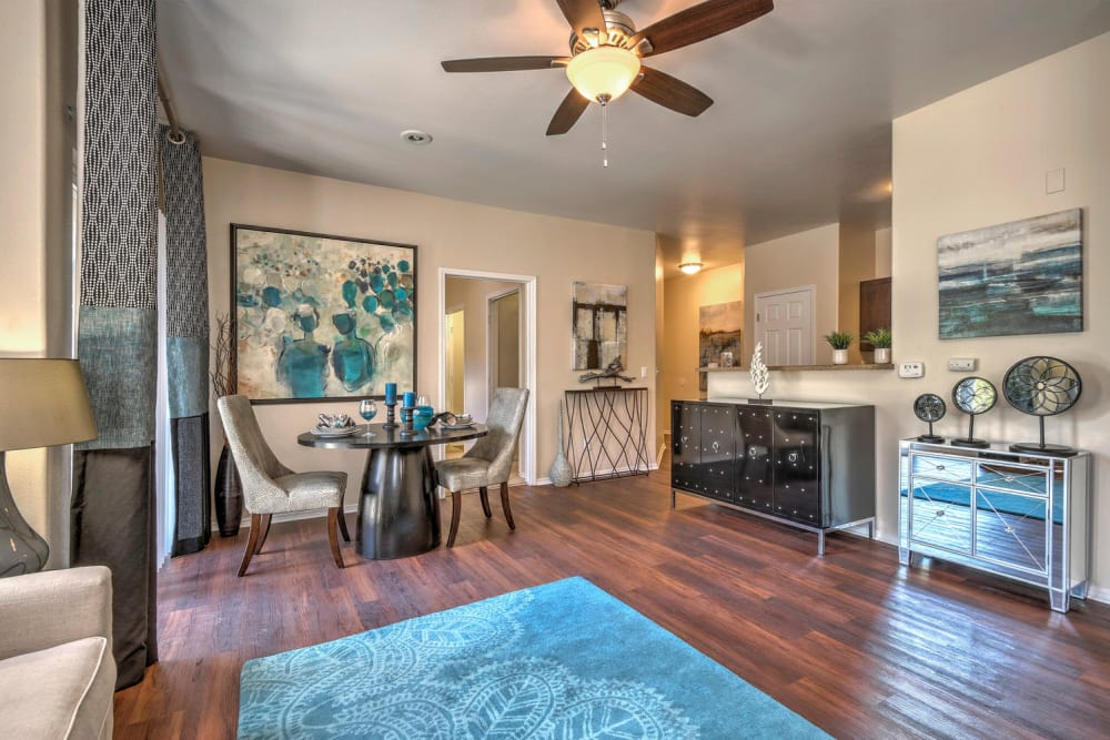 Living room and dining room with hardwood-style floors at Promenade at Hunter's Glen Apartments in Thornton, Colorado
