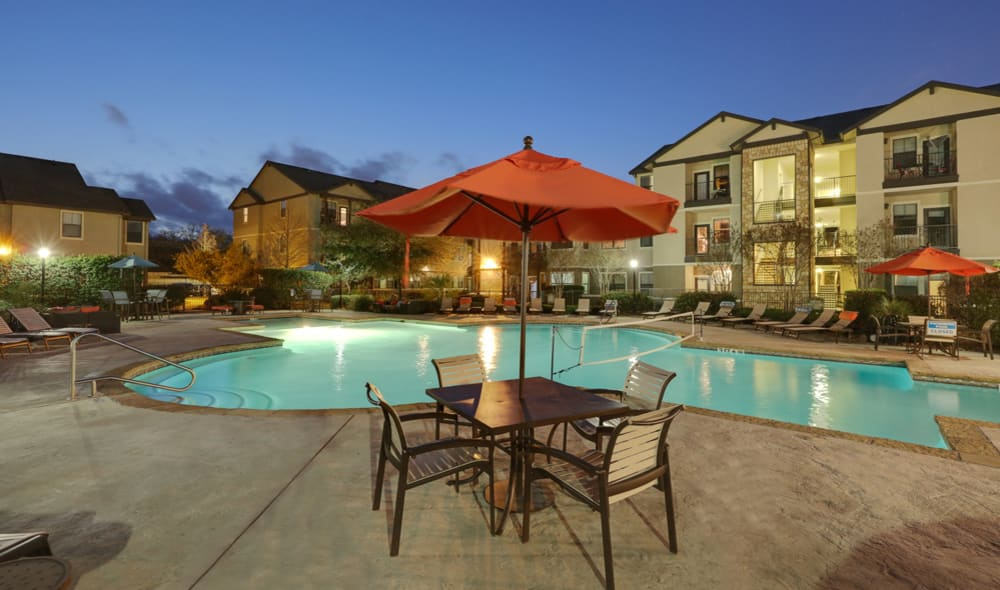 Covered table pool-side at Presidio Apartments in Bryan, TX, at night