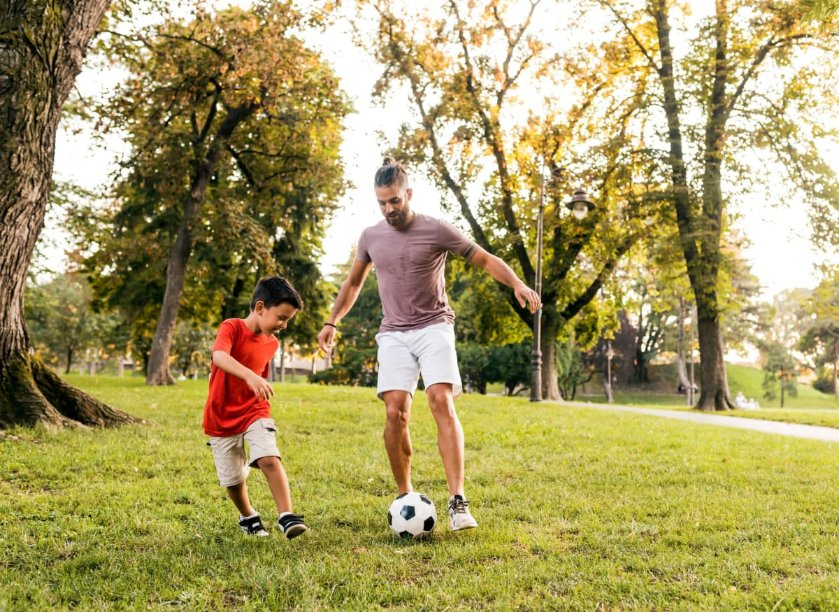 Family playing soccer at Clifton Ridge Apartments in Louisville, Kentucky