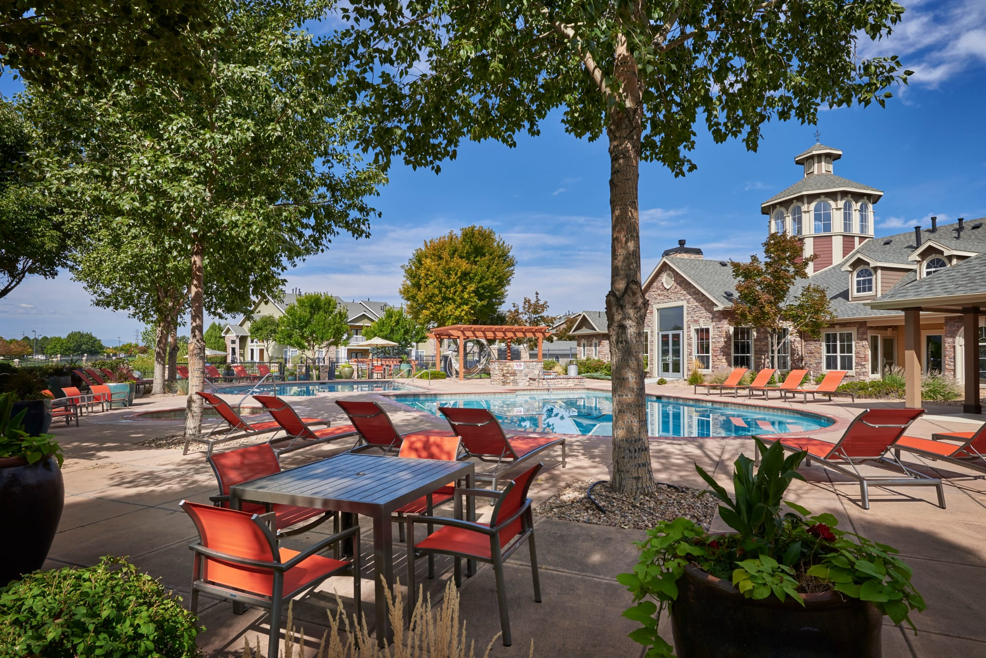 exterior pool view with tables and chairs at Gateway Park Apartments in Denver, CO