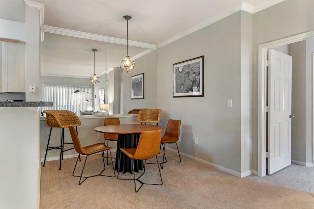 Modern dining table in front of a large mirror in a model apartment home at Regency at First Colony in Sugar Land, Texas