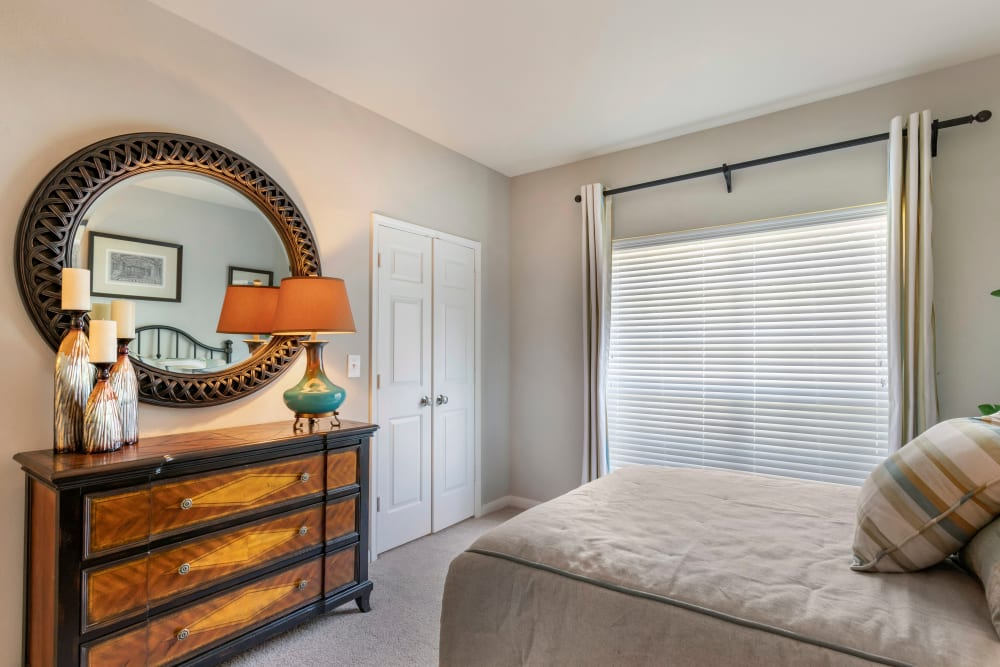 Model bedroom with a large mirror and spacious closet at Regency at First Colony in Sugar Land, Texas