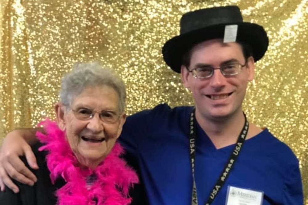 A resident and a staff member in front of a gold back drop at Spring Oaks in Brooksville, Florida
