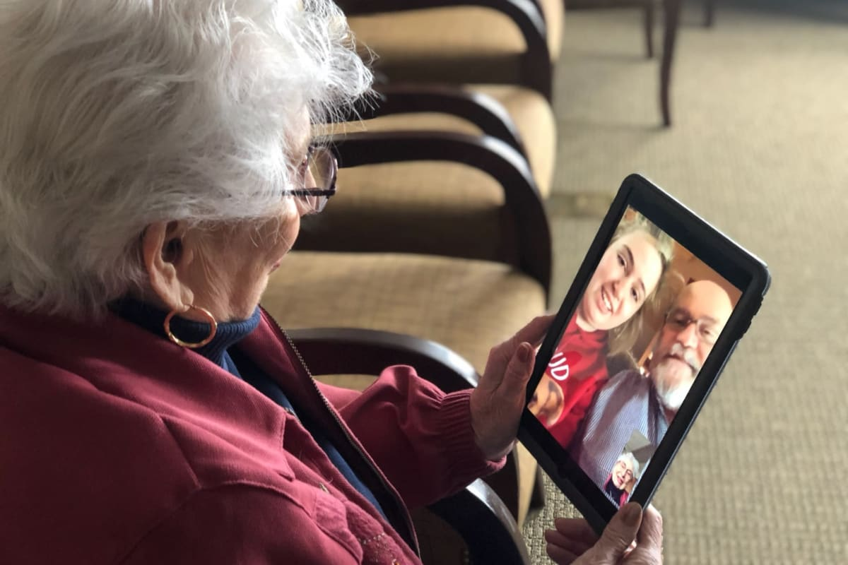 A resident using a tablet to communicate with her family safely at Oxford Senior Living in Wichita, Kansas