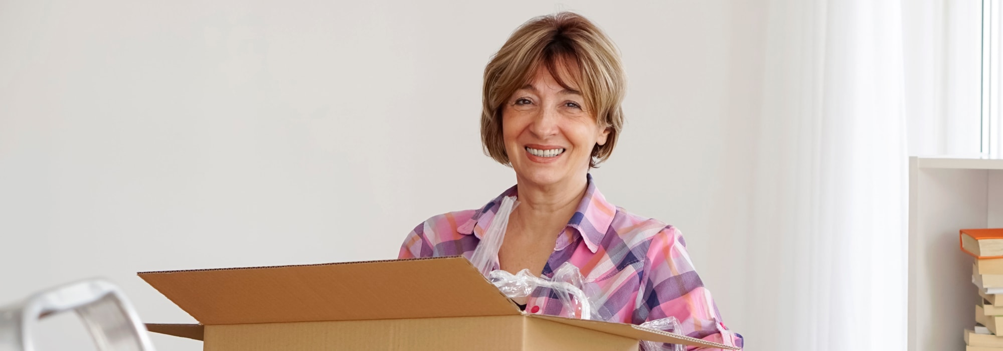 Happy woman moving boxes