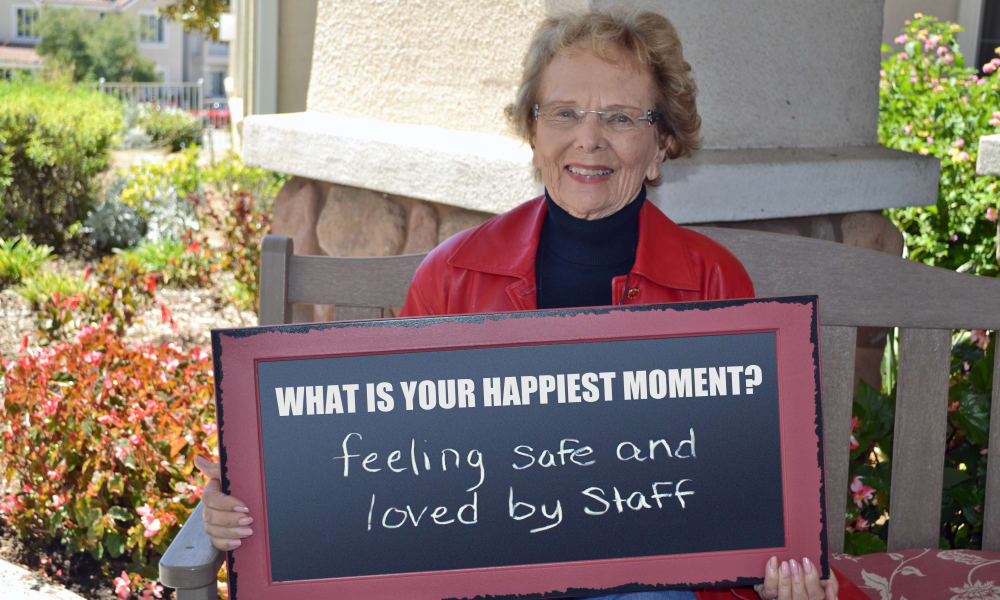 Happy resident at Alexis Estates Gracious Retirement Living in Allen, Texas, holding a chalkboard with her favorite community moment