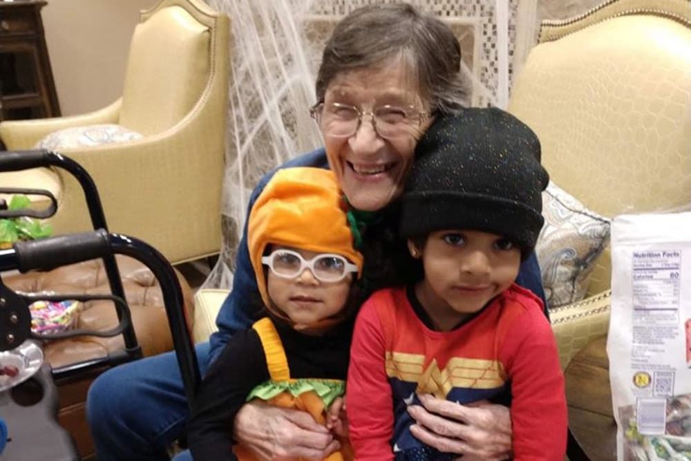 A resident holding her grandchildren at Inspired Living in Sugar Land, Texas