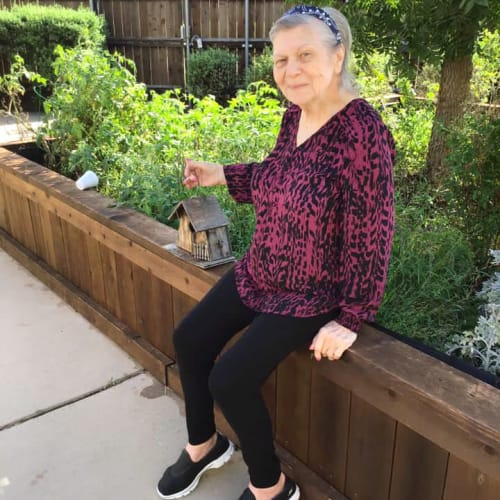 Resident sitting outside with a birdcage at Oxford Glen Memory Care at Grand Prairie in Grand Prairie, Texas