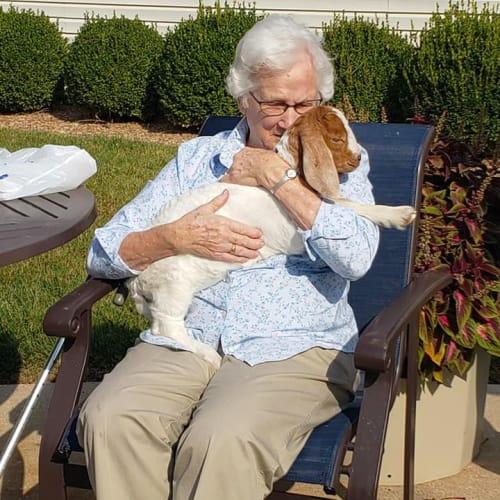 A resident sitting outside holding her dog at Alderbrook Village in Arkansas City, Kansas