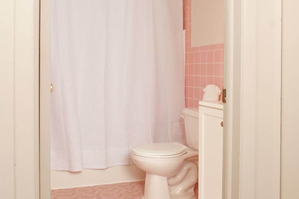 Bathroom with light pink tiled floor and walls at Alpine Court Apartments in Stratford, New Jersey