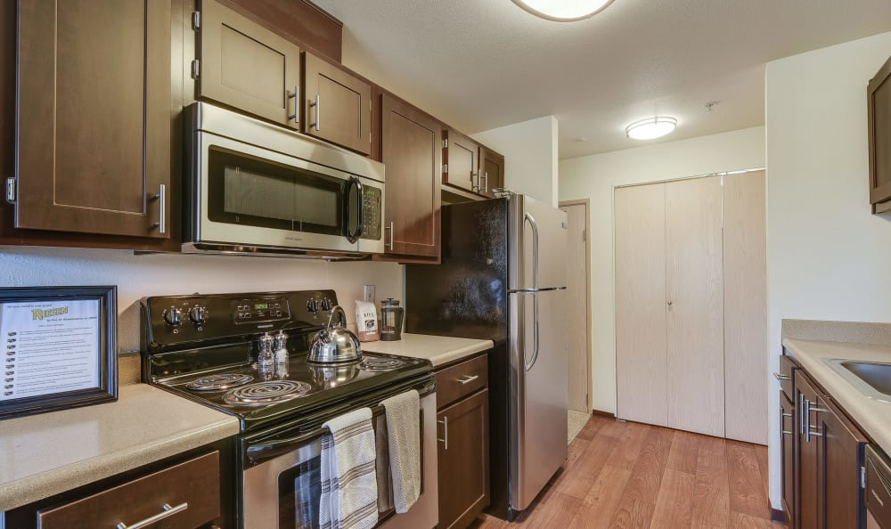 Brown Renovated Kitchen with stainless steel appliances at Renaissance at 29th Apartments