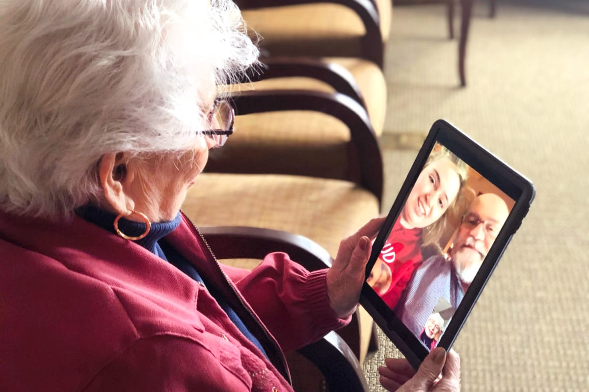 A resident using a smart phone at Oxford Glen Memory Care at Owasso in Owasso, Oklahoma