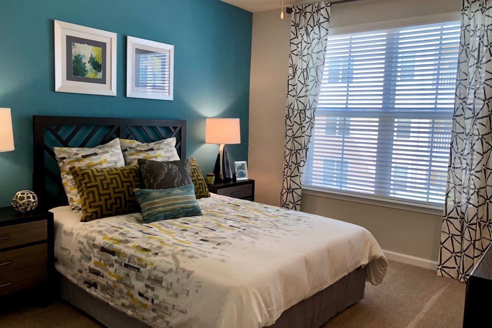 Bedroom decorated nicely with large windows at Level at 401 in Raleigh, North Carolina