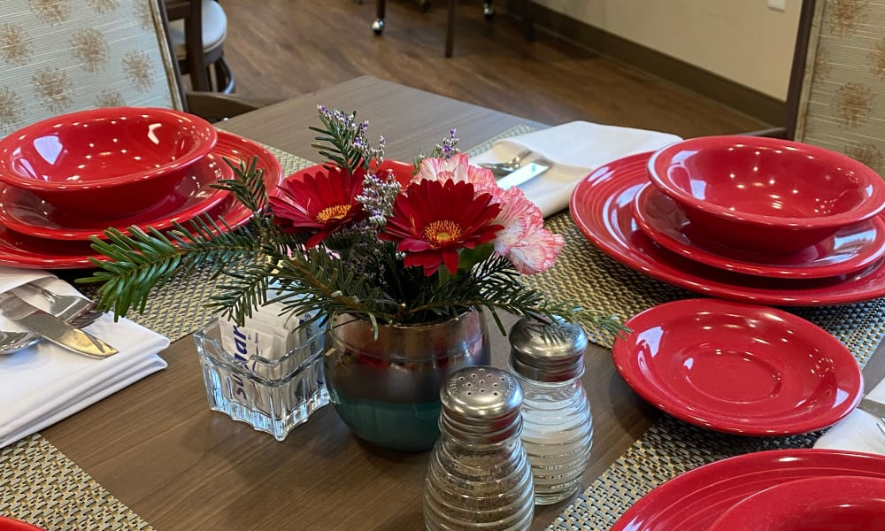 Dining table with bright red dishes at Quail Park Memory Care Residences of West Seattle in Seattle, Washington