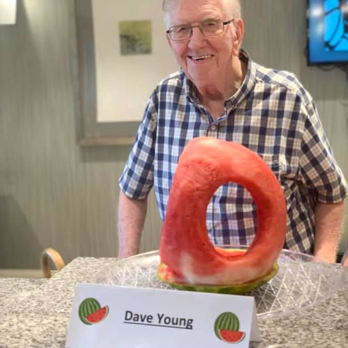 A resident standing next to his watermelon carving at Oxford Villa Active Senior Apartments in Wichita, Kansas