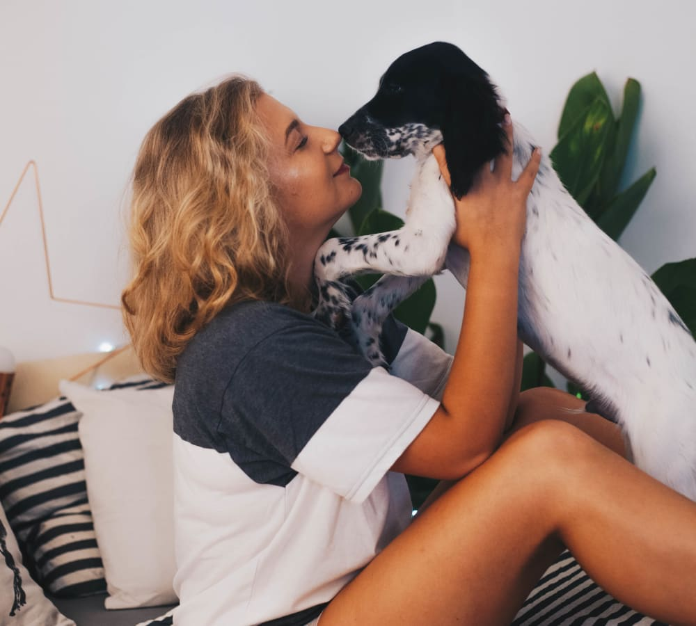 Resident giving her dog a kiss in their new home at Sofi Ventura in Ventura, California