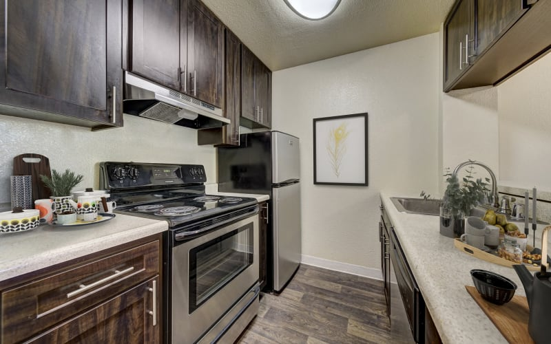 Espresso cabinets and hardwood-style floors in a kitchen at The Timbers Apartments in Hayward, California