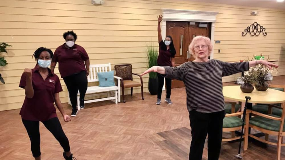 caretakers and residents dancing at Oxford Glen Memory Care at Carrollton in Carrollton, Texas