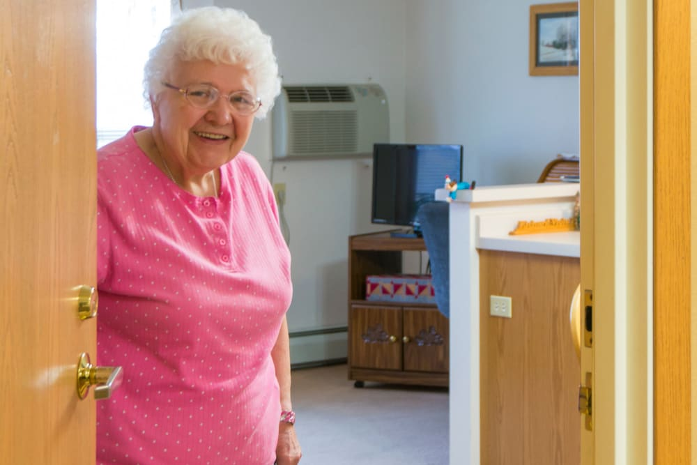 Resident welcomes visitor to her apartment at Meadow Lakes Senior Living in Rochester, Minnesota.